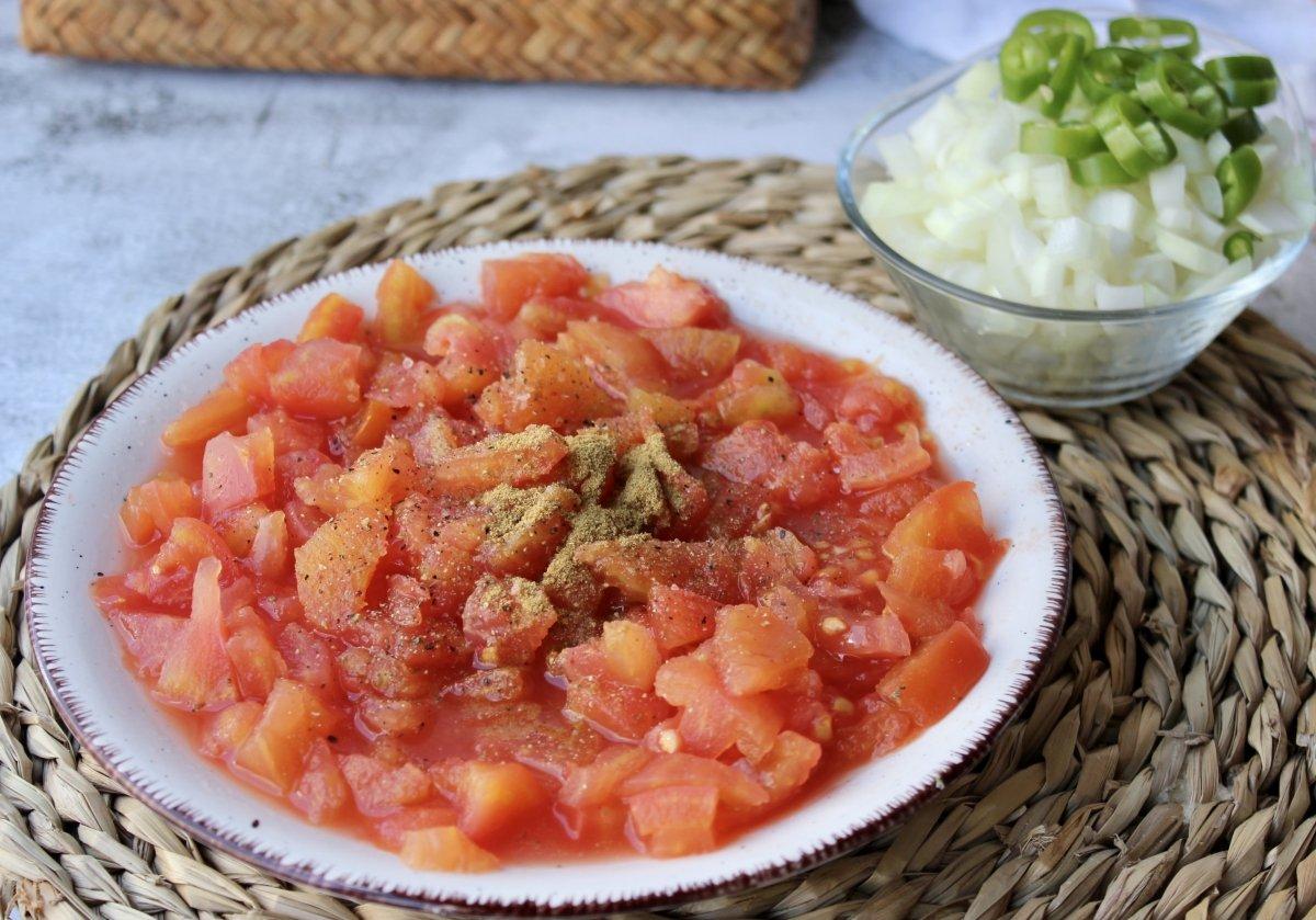 Tomate pera troceado en concassé junto con la cebolla y el chile serrano troceado para realizar sals
