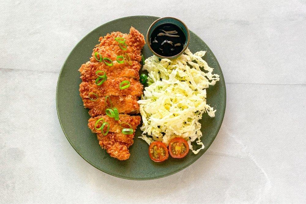 Tonkatsu acompañado de col y salsa