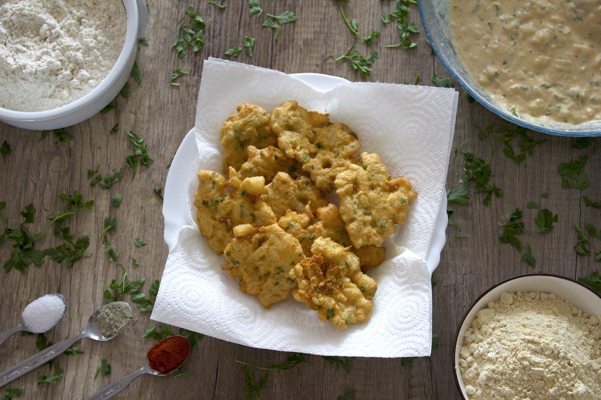 Tortillitas de bacalao escurriendo en un plato con papel absorbente
