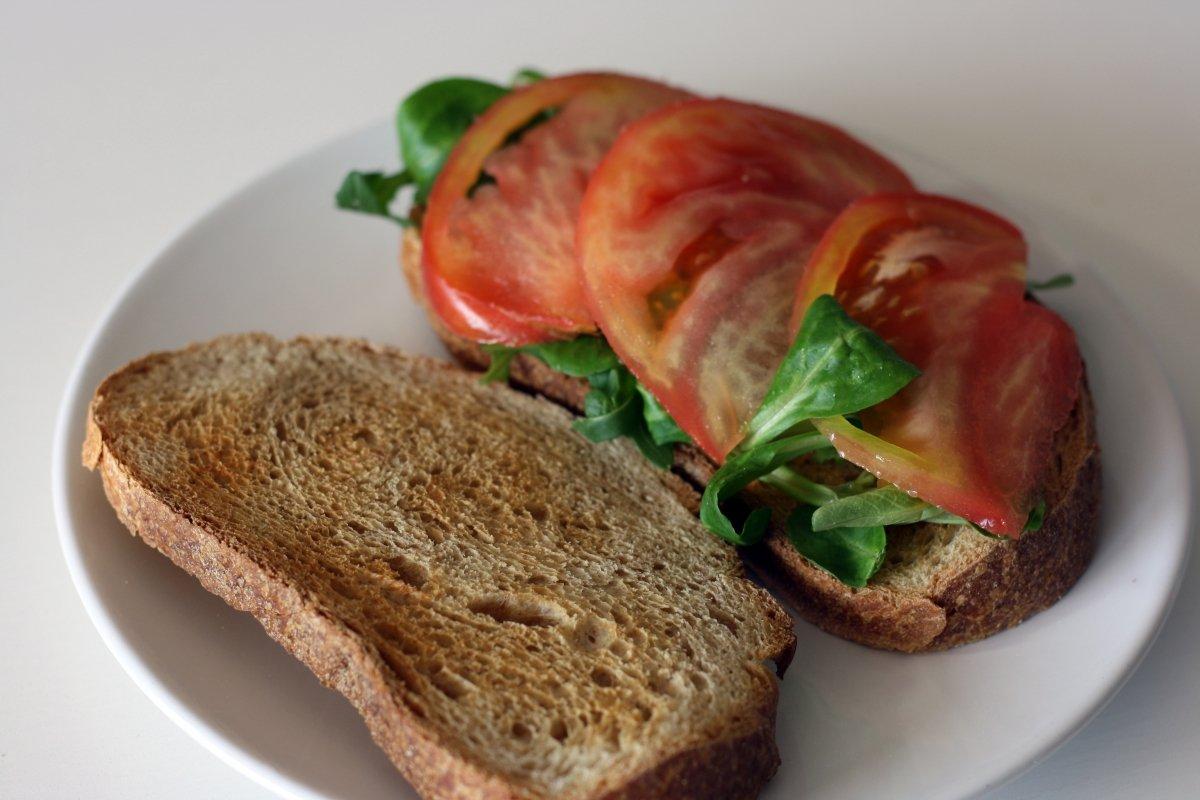 Tostar el pan y montar con tomate y hojas verdes