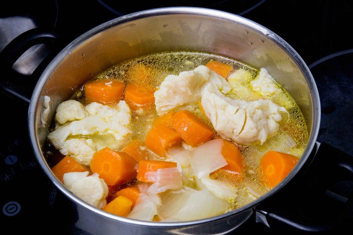 Triturar y salpimentar las verduras para hacer la crema de coliflor y zanahoria