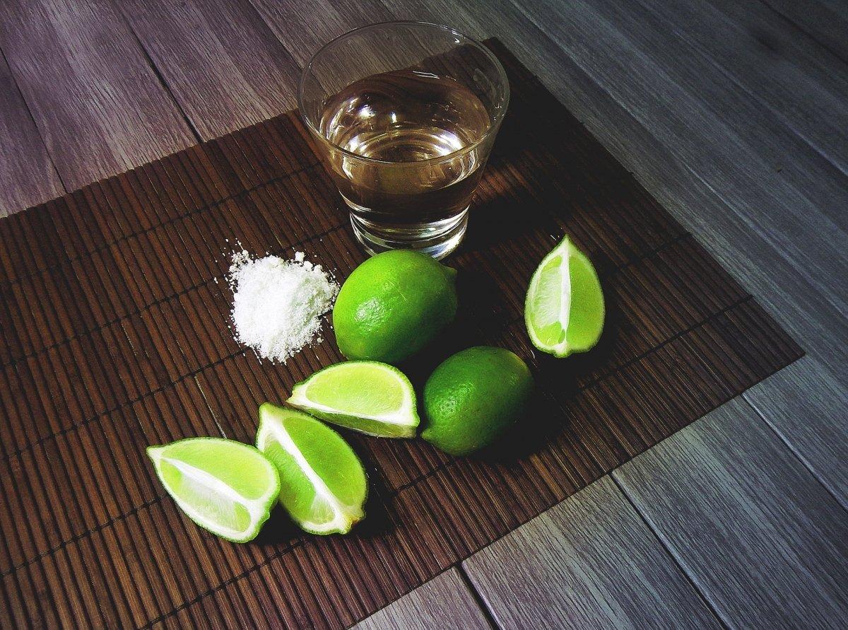 Un vaso de tequila con sal y limón
