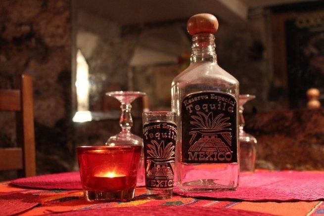Una botella de tequila junto a un vaso