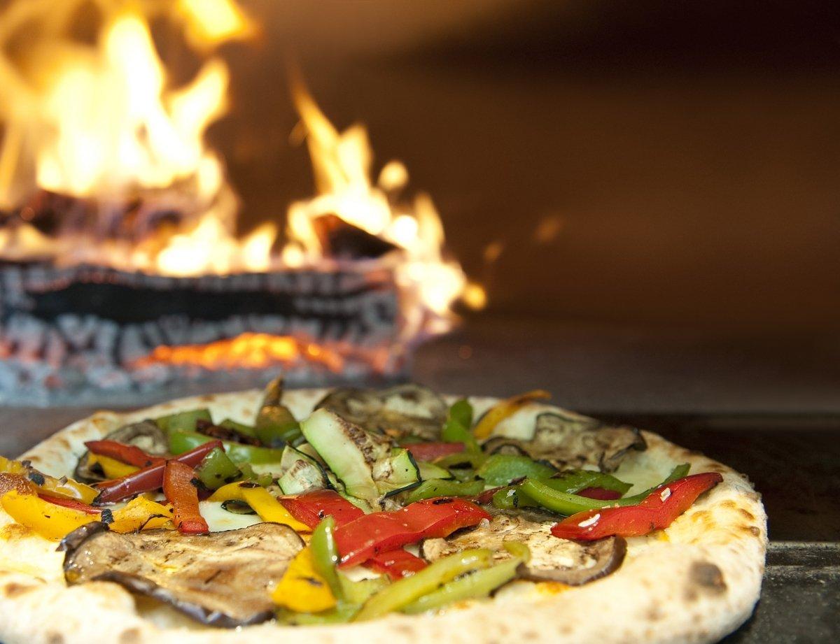 Una pizza del restaurante Bosco de Lobos cocinándose a la leña