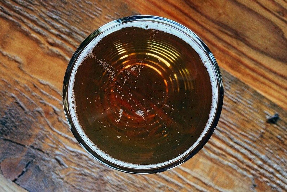 Vaso de cerveza sobre mesa de madera