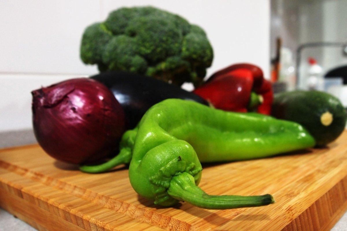 Verduras crudas sobre tabla de cortar para preparar raw food