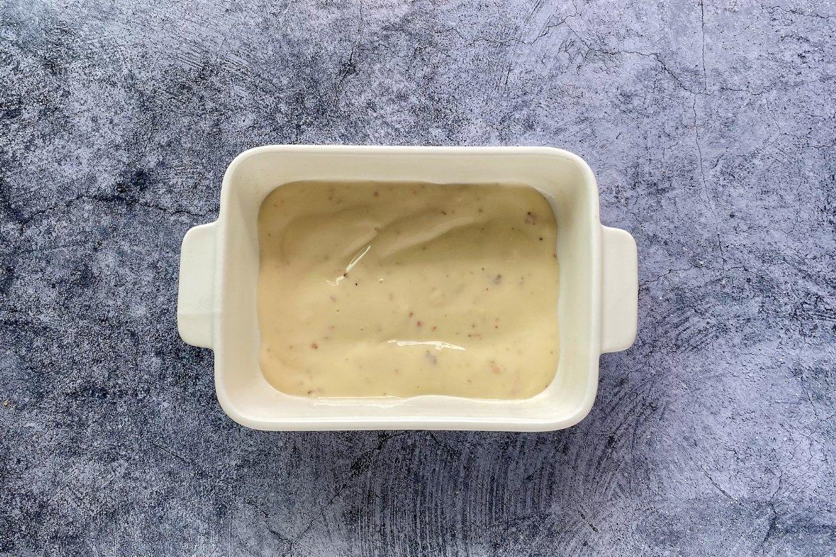 Verter salsa bechamel en el fondo de la cazuelita