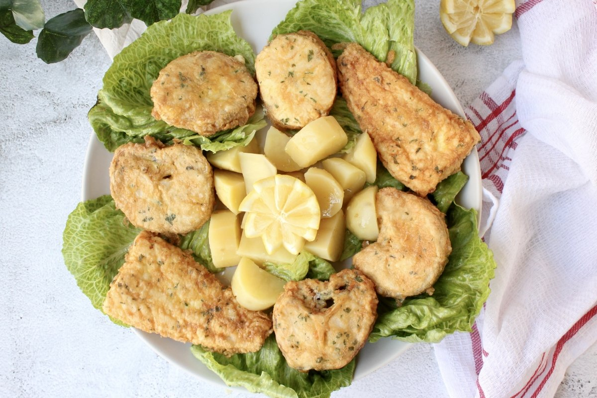 vista cenital del emplatado de la merluza a la romana con patatas cocidas como guarnición