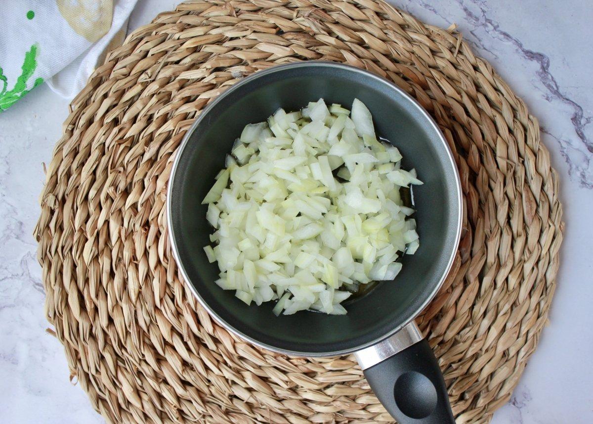 Vista de la sartén con aceite de oliva, cebolla troceada y sal para ser pochada