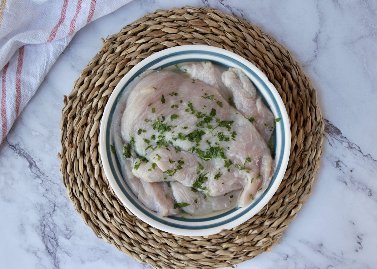 Vista de las pechugas de pollo con zumo de limón y perejil para marinar