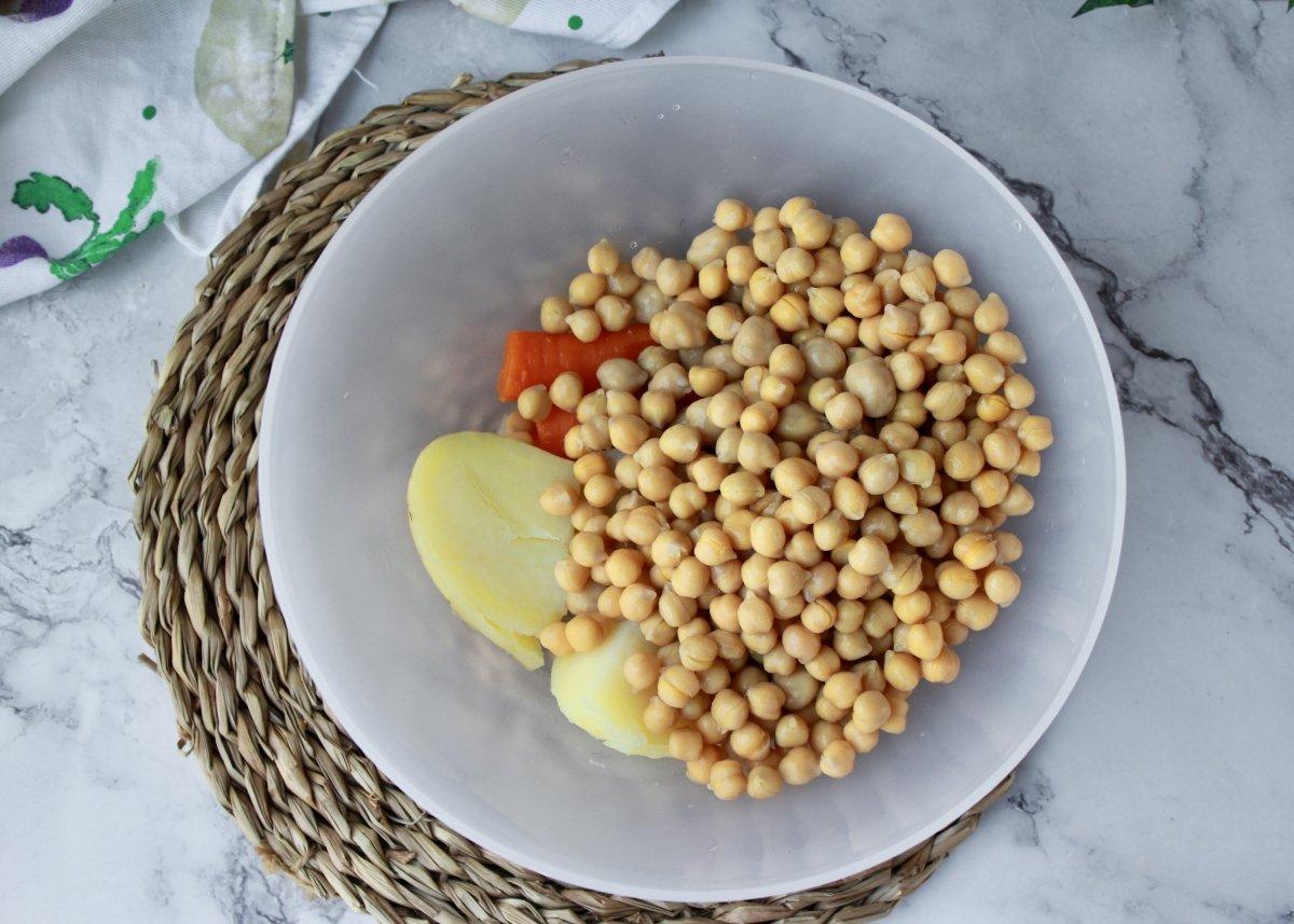 Vista del bol con la patata, la zanahoria y los garbanzos cocidos para triturar