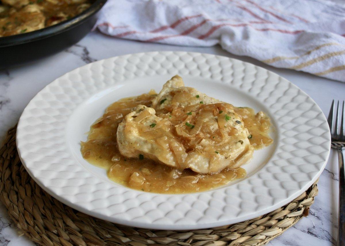 Vista del plato con pechuga de pollo y cebolla servido en la mesa
