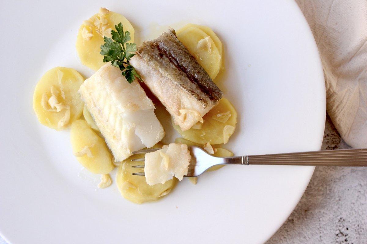 vista del plato de bacalao confitado comprobando la jugosidad de las lascas