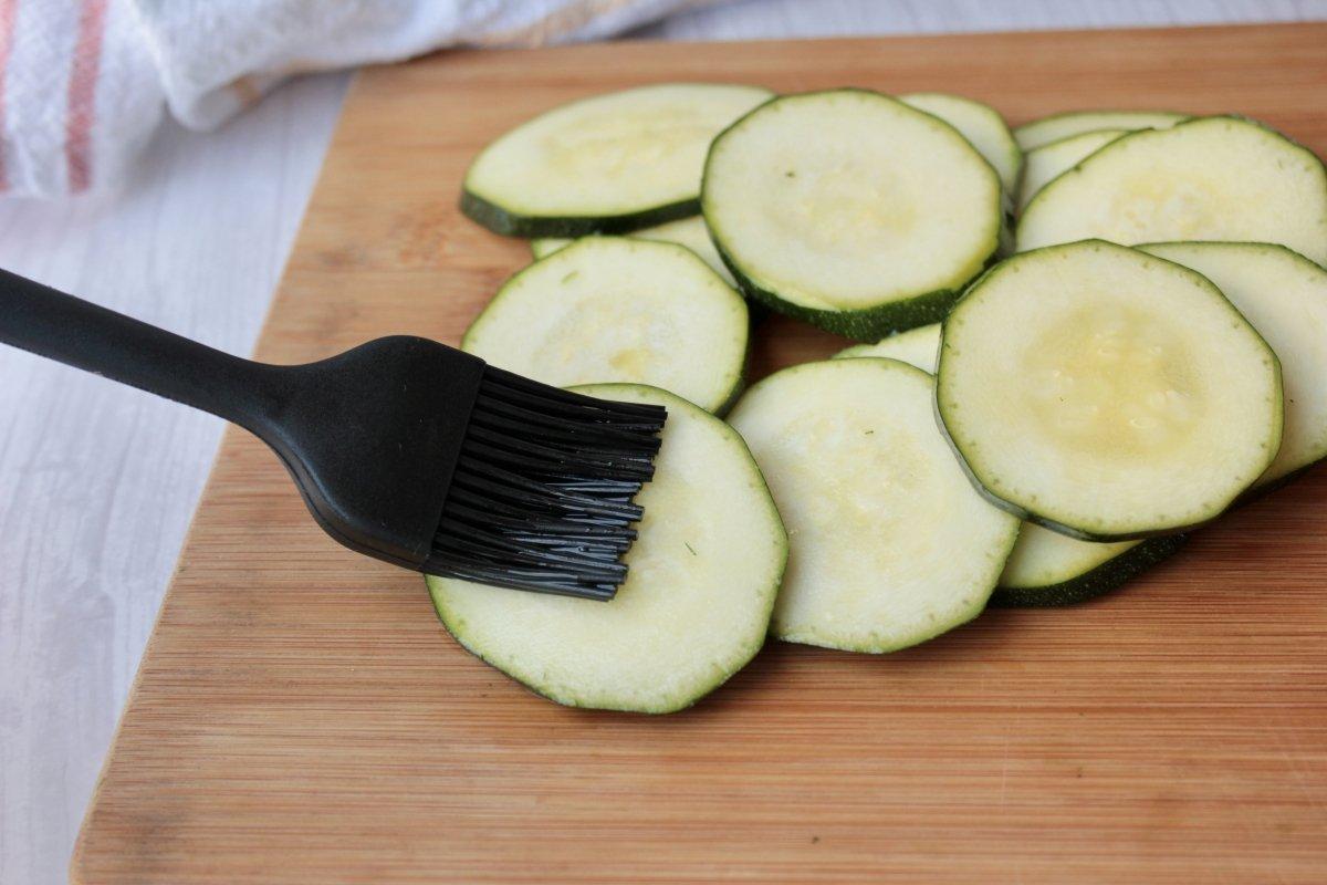 Vista del proceso de pincelar los calabacines con aceite de oliva previa su cocción